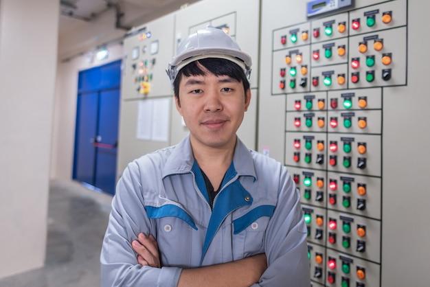 Инженер работает и проверяет состояние распределительного устройства распределения электрической энергии в помещении подстанции электростанции Premium Фотографии