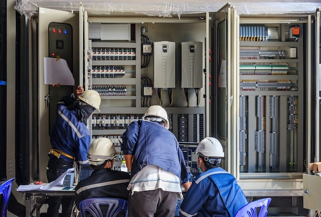 Engineer working on checking and maintenance equipment at wiring on plc cabinet Premium Photo
