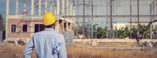 Engineer working on construction site with drawing document Premium Photo