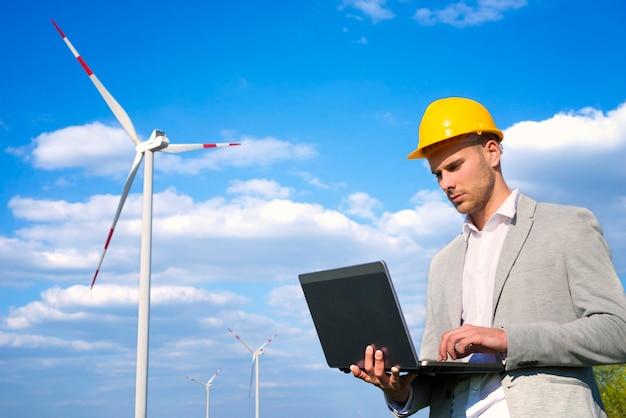 Ingegnere che lavora al suo computer portatile davanti a generatori eolici Foto Gratuite