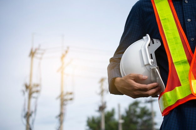Engineering holds white safety hats and electric pole background Premium Photo