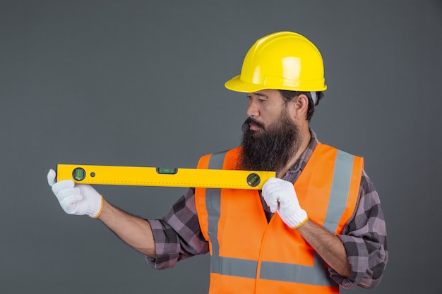 An engineering man wearing a yellow helmet holding a water level meter on a gray . Free Photo