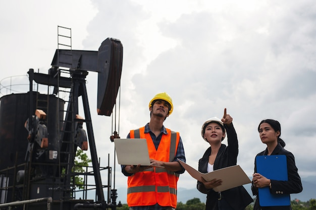 The engineering team stands beside working oil pumps with a sky . Free Photo