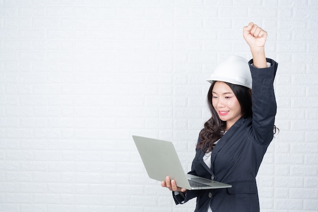 Engineering woman holding a separate notebook, white brick wall made gestures with sign language. Free Photo