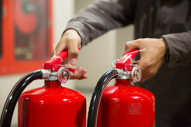 Engineers are checking handle of fire extinguishers. Premium Photo