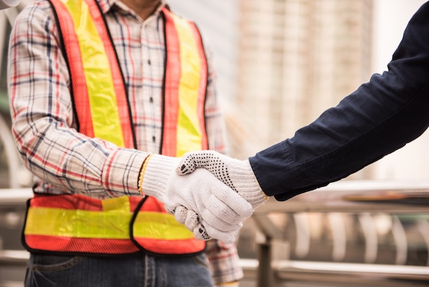 Engineers and businessmen handshake for collaborate to plan the building. Premium Photo