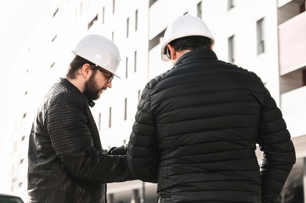Engineers discussing plans on street Free Photo