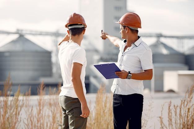 工場のそばに立っているヘルメットのエンジニア 無料写真