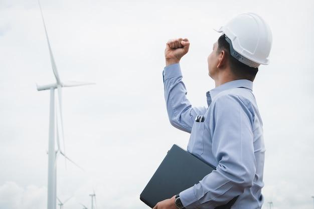 엔지니어는 얼굴 마스크를 착용하고 백그라운드에서 풍력 터빈으로 노트북에서 작업하는 풍차 프리미엄 사진