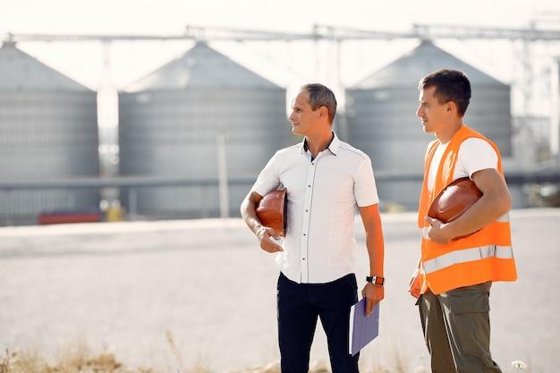 Ingegneri con caschi in piedi accanto alla fabbrica Foto Gratuite