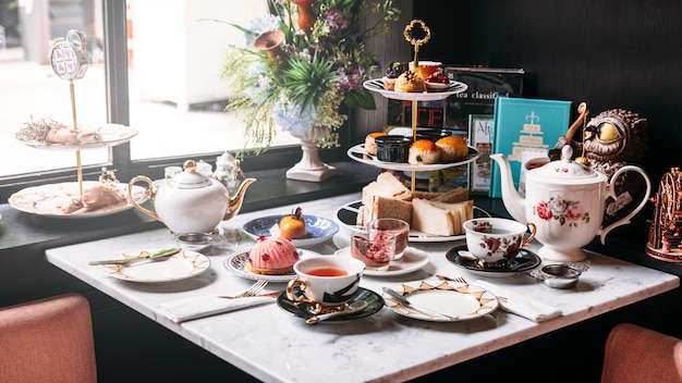 English afternoon tea set including hot tea, pastry, scones, sandwiches and mini pies. Premium Photo