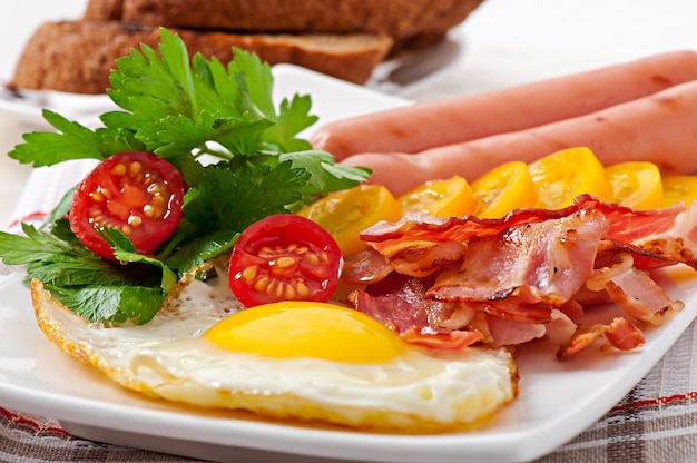 English breakfast - fried eggs, bacon, sausages and toasted rye bread Free Photo