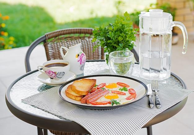 サマーテラスでのイングリッシュブレックファスト:目玉焼き、ソーセージ、トマト、トースト。一杯のコーヒー。ホテルの朝食のクローズアップ。 Premium写真