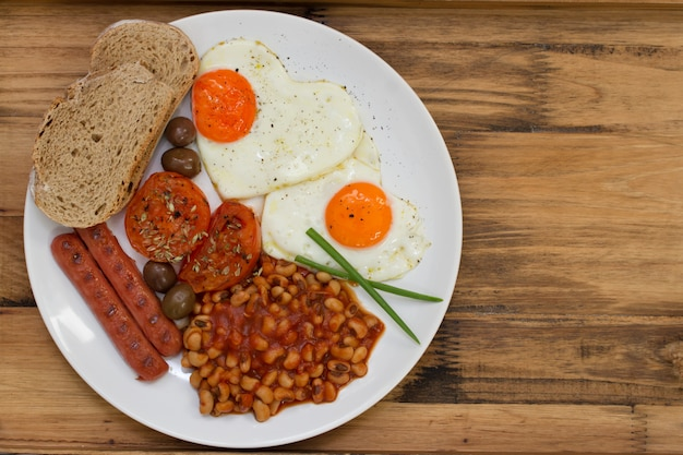 English breakfast on white plate on brown wooden table Premium Photo