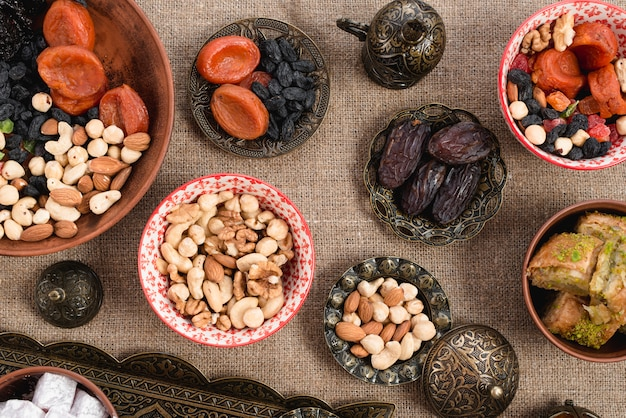 Engraved metallic; copper and ceramic bowl with dried fruits and nuts on jute tablecloth Free Photo