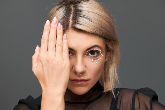Enigmatic trendy young european woman with blonde dyed hair and crystals on her face as part of make up, covering one eye with palm, showing polished nails. art and cosmetics Free Photo