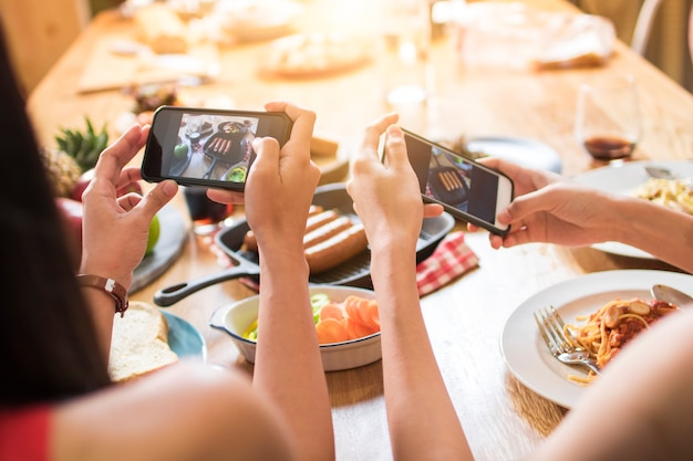 Enjoy dinner eating party with friends and taking photo by phone to post into Premium Photo