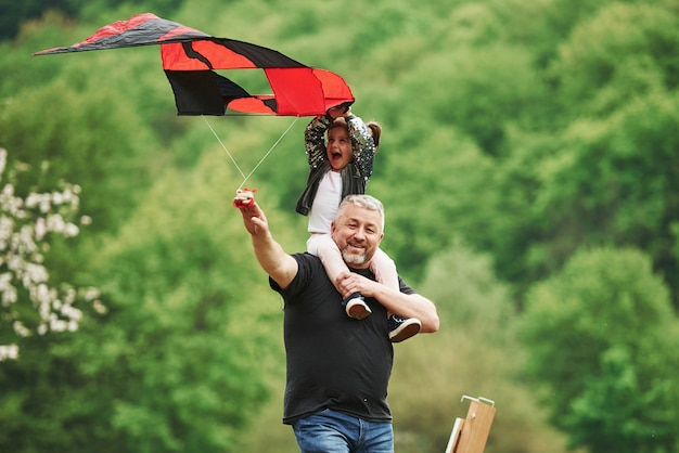 Enjoy the moment. running with red kite. child sitting on the man's shoulders. having fun Free Photo