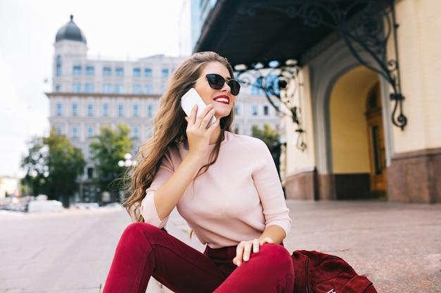 La ragazza goduta con l'acconciatura lunga si sta rilassando sulle scale in città. indossa pantaloni vinosi, parla al telefono e sorride di lato. Foto Gratuite