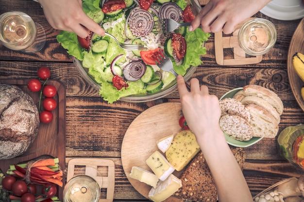 友達とディナーを楽しんでいます。一緒に夕食を食べている人々のグループのトップビュー 無料写真