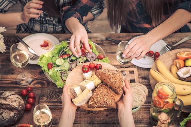 Gustando la cena con i miei amici. vista dall'alto di un gruppo di persone che cenano insieme, seduti a un tavolo in legno rustico, il concetto di festa e sano cibo cucinato in casa Foto Gratuite