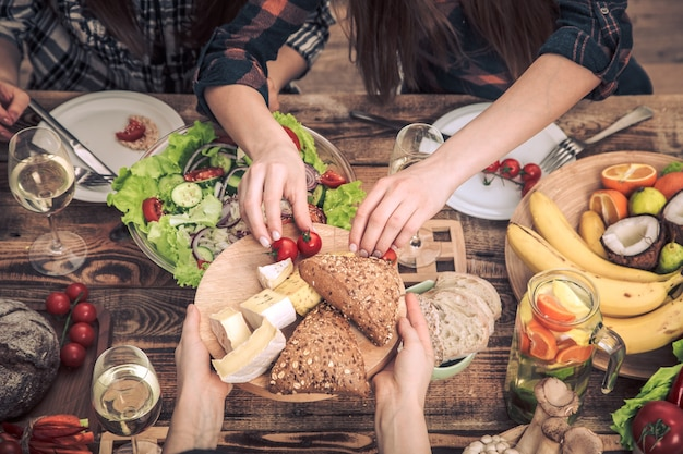 友達とディナーを楽しんでいます。素朴な木製のテーブル、お祝いの概念、健康的な家庭料理に座って、一緒に食事をする人々のグループの平面図 無料写真