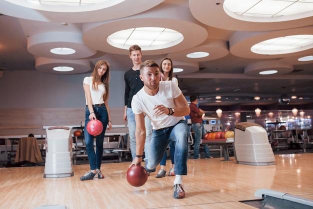 Godersi il gioco. i giovani amici allegri si divertono al bowling durante i fine settimana Foto Gratuite