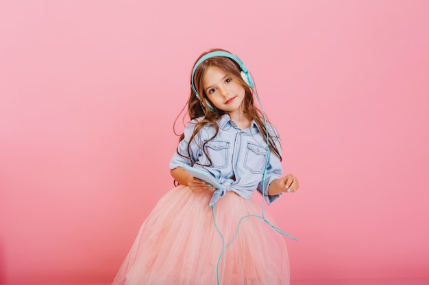 Ascoltare musica adorabile attraverso la testa blu [pietre di bambina carina con lunghi capelli castani isolati su sfondo rosa. bambino alla moda in gonna di tulle che esprime vere emozioni positive alla telecamera Foto Gratuite