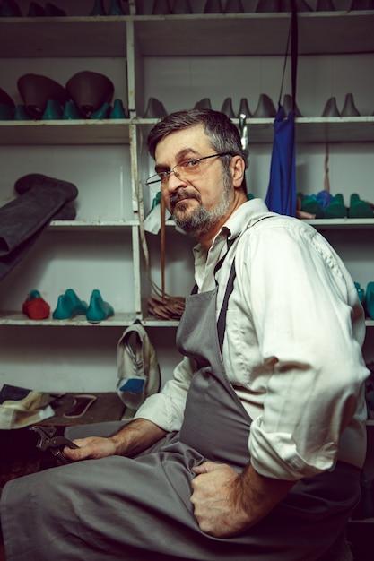 Смотрим процесс создания обуви на заказ. рабочее место дизайнера обуви. руки сапожника с инструментом сапожник Бесплатные Фотографии