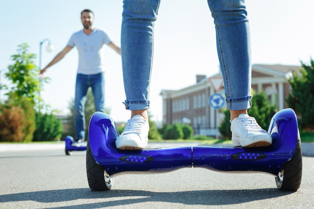 Enjoying the ride. the close up of female legs in jeans standing on a blue hoverboard while a cheerful man riding the same one in the background Premium Photo