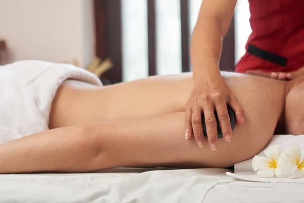 Enjoying stone massage at spa salon Free Photo