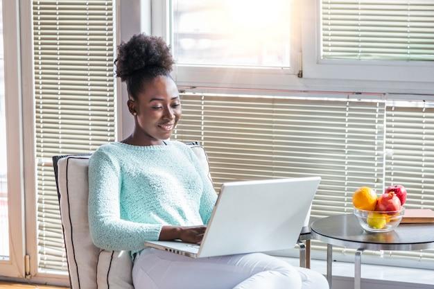 Наслаждаясь временем дома. красивая молодая улыбается женщина работает на ноутбуке и пить кофе, сидя в большом удобном кресле у себя дома Premium Фотографии