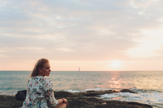 Enjoying vacation. young traveling woman enjoying sunset on sea view point. Premium Photo