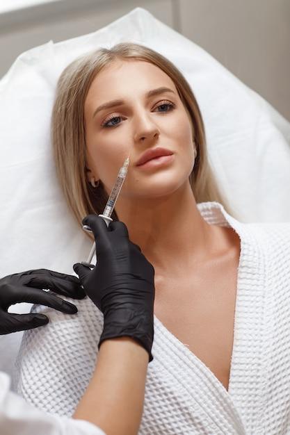 Увеличение губ, коррекция губ. портрет белой женщины во время операции заполнения морщин на лице. пластическая хирургия. молодая женщина получает косметические инъекции в губы Premium Фотографии