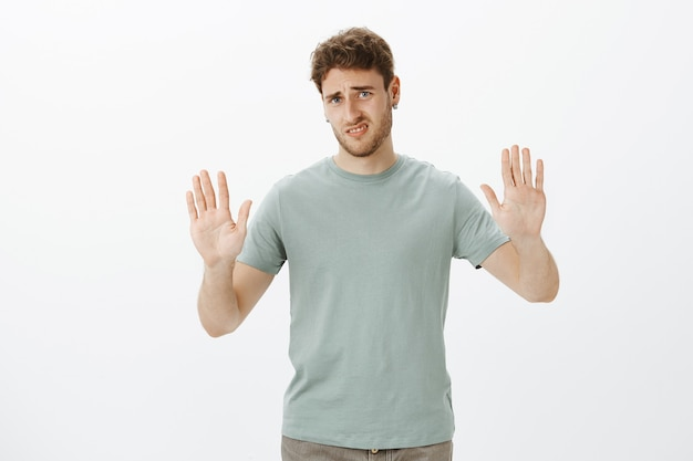Enough, do not bother me. displeased and disgusted charming man in t-shirt, pulling hands towards in rejection gesture Free Photo