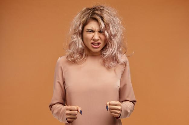 Взбешенная разъяренная молодая женщина с пышными волосами, сжимая кулаки и ревущая, выражая свой гнев Бесплатные Фотографии