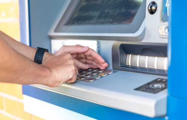 Entering a credit card pin on an atm keyboard Premium Photo
