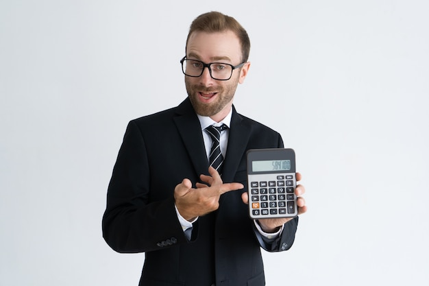 Enterprising bearded businessman pointing at calculator Free Photo