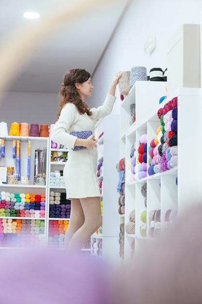 Enterprising young woman organizing wools at a retail business Premium Photo