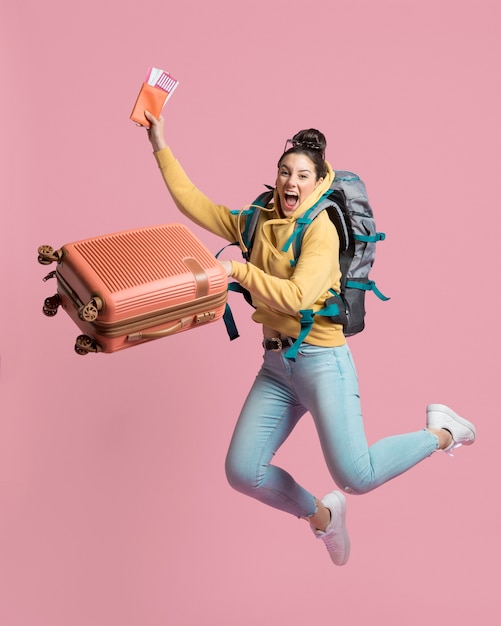 Enthusiast woman holding her baggage and plane ticket Premium Photo