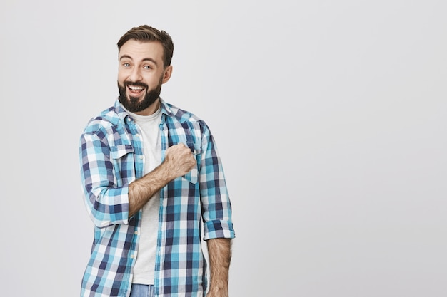 Enthusiastic adult bearded man fist pump, boost confidence Free Photo