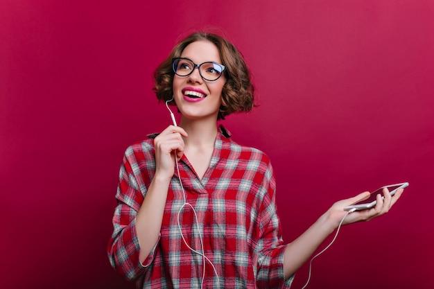 Восторженная девушка в наушниках с удовольствием позирует на бордовой стене. фотография в помещении вдохновленной кудрявой молодой женщины в очках и слушающей музыки. Бесплатные Фотографии
