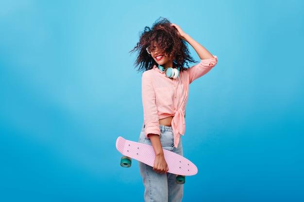 Восторженная девушка с коричневым наслаждением вьющейся прической. стройная африканская девушка со скейтбордом, играя с волосами и смеясь. Бесплатные Фотографии