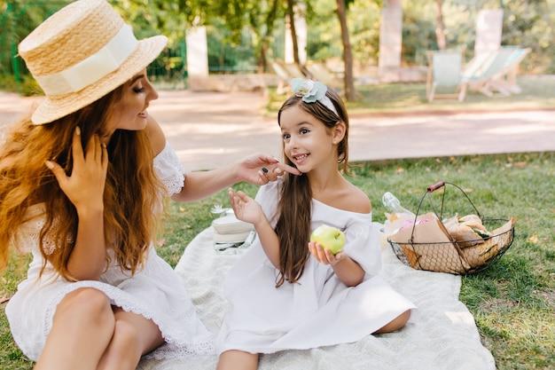 青リンゴを保持し、お母さんと話している長い茶色の髪の熱狂的な女の子。公園で毛布の上に座っている間、指で娘の顔に触れるエレガントな帽子のきれいな女性。 無料写真