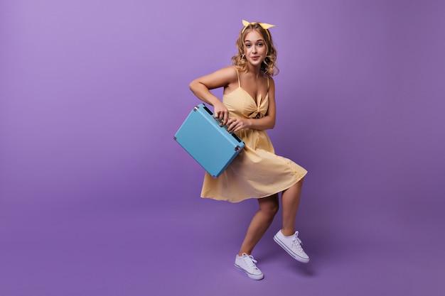 旅行前にうろついているウェーブのかかった髪型の熱狂的な女の子。青いスーツケースで踊るのんきな金髪女性の肖像画。 無料写真
