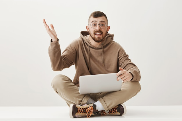 Enthusiastic guy discuss something while sitting on crossed legs with laptop Free Photo