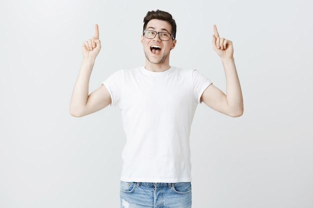Studente maschio entusiasta in bicchieri che invitano all'evento, puntando le dita verso l'alto Foto Gratuite
