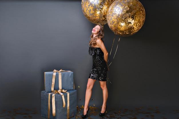 Восторженная белая девушка с блестящими гелиевыми шарами наслаждается фотосессией на день рождения. очаровательная женская модель в черном платье позирует с большими настоящими коробками и улыбается. Бесплатные Фотографии
