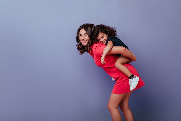 Enthusiastic woman in short dress playing with curly kid on purple wall. indoor photo of laughing young lady and her little daughter. Free Photo