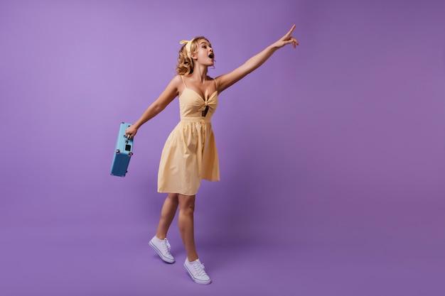 何かに指を指している手に青いスーツケースを持つ熱狂的な女性。黄色のドレスを着た面白い好奇心旺盛な女の子の全身像。 無料写真